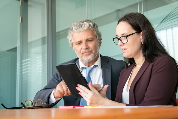 深刻な焦点を合わせた同僚がタブレットを一緒に使用し、オフィスのテーブルに座っているときにガジェット画面を見て指さします。