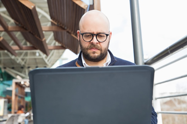 Serious focused freelancer using laptop