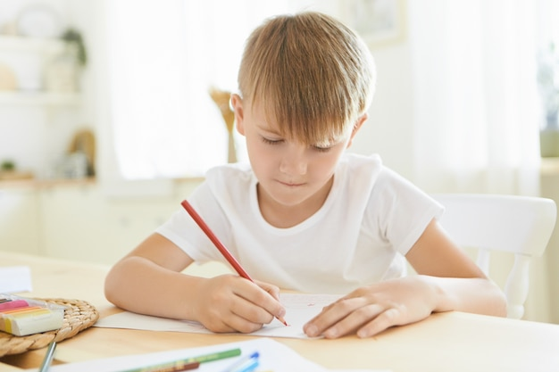 Serious focused schoolboy in white t-shirt entertaining himself indoors using red pencil drawing or sketching at wooden table isolated against stylish living room