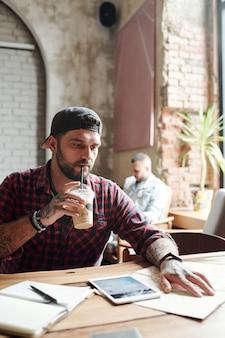 Серьезный сосредоточенный молодой бородатый мужчина с татуировками сидит за столиком в кафе и пьет коктейль, планируя поездку с помощью карты