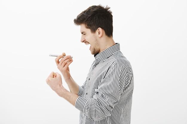Серьезный сосредоточенный молодой темноволосый мужчина стоит в профиль и держит смартфон возле рта, сжимает кулак, поет на устройстве или разговаривает по динамику через серую стену, играет в караоке