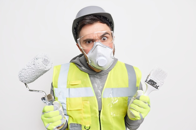Serious foreman holds building tools looks attentively through safety glasses wears uniform busy remodeling house