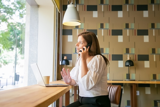공동 작업 공간에서 노트북과 커피와 함께 책상에 앉아있는 동안 휴대 전화로 이야기하는 심각한 프리랜서 전문가