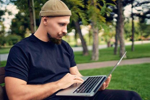 진지한 프리랜서는 노트북 g 인터넷 연결에서 작업하는 텍스트를 입력하는 동안 야외에 앉아 있습니다.