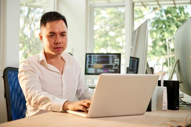 彼のオフィスの机でラップトップに取り組んでいる深刻なしかめっ面のソフトウェア開発者