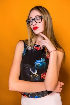 The serious frustrated young beautiful business woman on orange wall