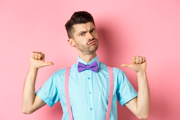 Serious and funny young man trying look cool, pointing at himself to self-promote, being a professional, standing over pink background.
