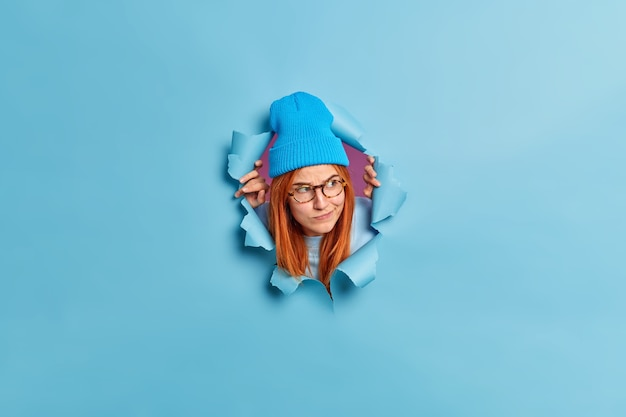 Serious ginger millennial girl in blue hat and spectacles looks puzzled away purses lips.