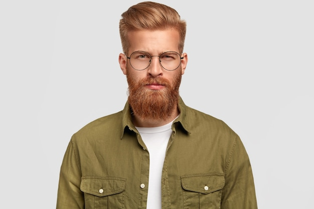 Serious ginger stylish man has thick beard and mustache, dressed in green shirt, looks seriously