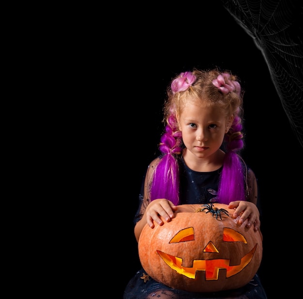 A serious girl in a carnival costume of a little witch playing with an orange pumpkin and a spider.