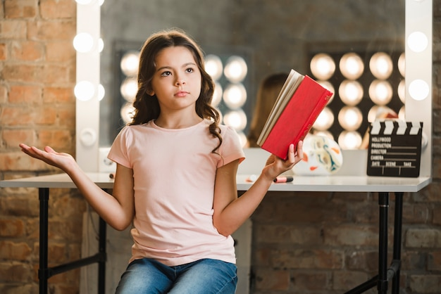 Serious girl holding red book in her hand shrugging