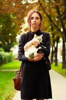 Serious girl hugging her cat in the park