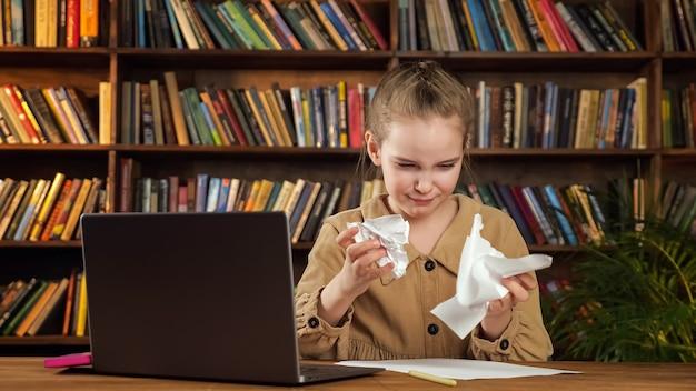 갈색 재킷을 입은 진지한 소녀는 큰 책꽂이가 있는 집에서 검은색 노트북 옆에 앉아 분노한 후 실수로 에세이와 눈물 종이를 씁니다.