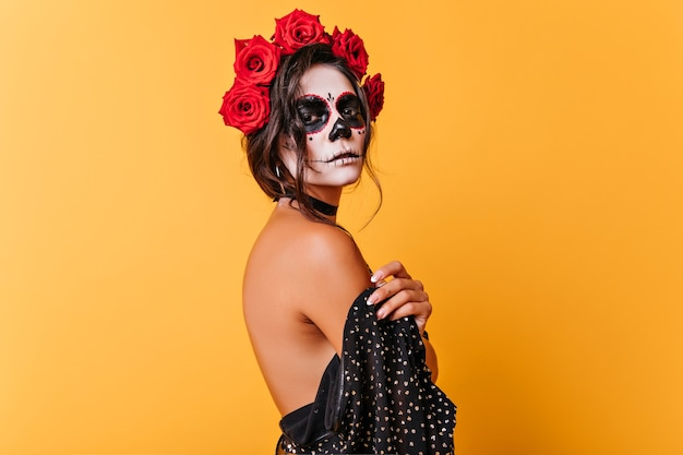할로윈 사진 촬영 동안 카메라를 찾고 la muerta 복장에 심각한 소녀. 노란색 배경에 고립 된 검은 머리에 장미와 매력적인 죽은 신부.