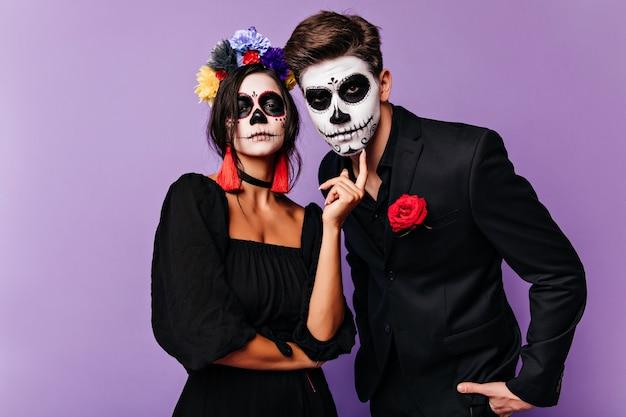 紫色の背景にポーズをとる仮面舞踏会の衣装を着た真面目な女の子。カメラを探しているカーニバルの服装の面白いカップル。