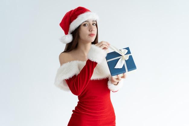 Серьезная девушка в новогодней шапке открывает рождественский подарок