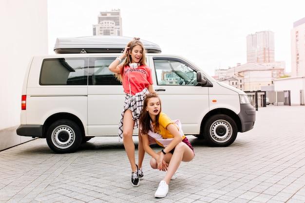 그녀의 긴 머리를 만지고 웃고 분홍색 옷차림에 친구 옆에 광장에 앉아 노란색 셔츠에 심각한 소녀