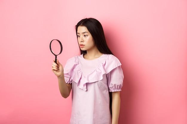 ピンクの背景に立って、調査し、虫眼鏡を通して見て、何かを探している深刻な女の子。
