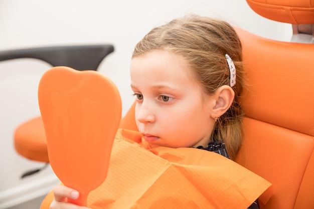 Серьезная девушка смотрит в зеркало в кресле стоматолога