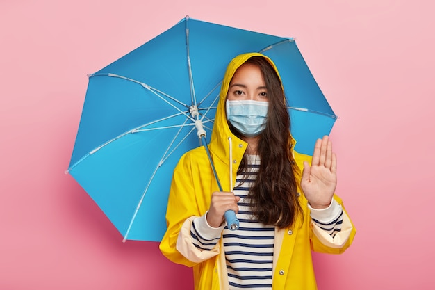 Serious girl makes stop gesture, asks not pollute environment, walks in acid rain, wears protective mask to reduce breathing pollutants, wears raincoat, hides under umbrella