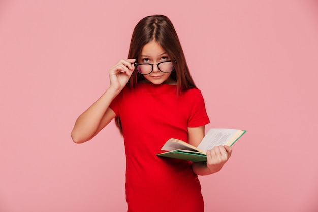 Serious girl nerd in dress looking through glasses while reading