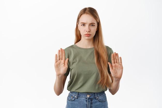 차단하기 위해 손을 들고 있는 진지한 소녀, 아니오라고 말하며 행동을 승인하지 않고 나쁜 것을 거부하고 불쾌한 얼굴을 하고 제안을 거부하고 흰 벽에 기대어 서 있습니다.