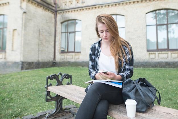 真面目な女の子がキャンパスのベンチに座って、球体に関する本を持ち、スマートフォンを使用しています。