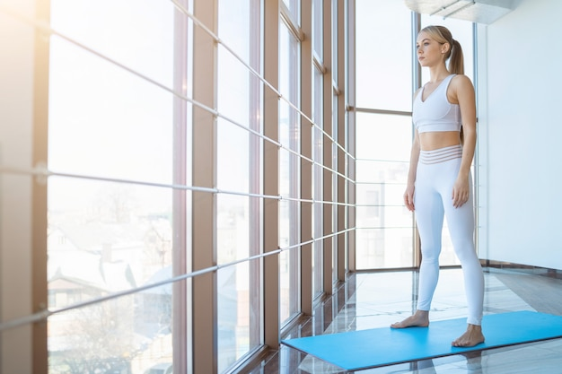 Serious girl in sportswear stands in the room