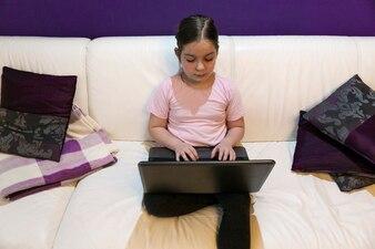 Serious girl using laptop on sofa
