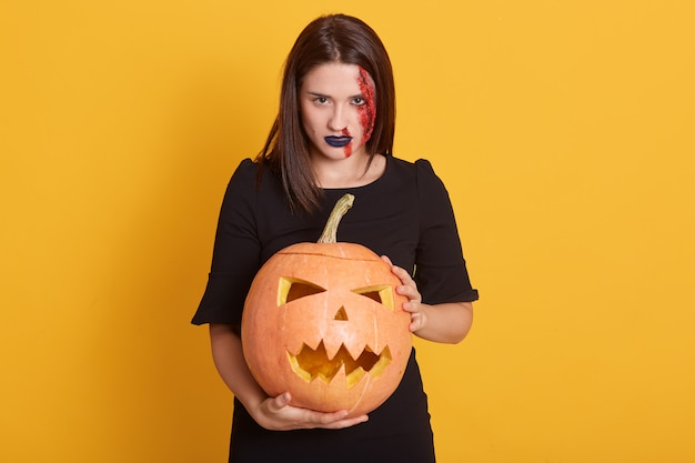Serious girl with angry facial expression standing with pumpkin in hands in studio isolated on yellow, attractive female with bloody wound on her face, halloween concept.
