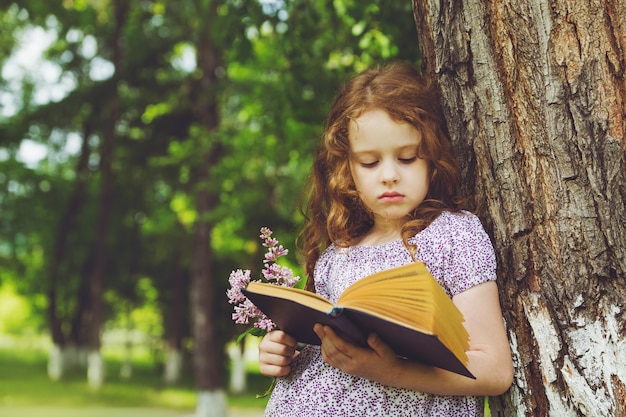 Serious girl with a book and a bouquet of lilacs in her hand, standing near large tree.