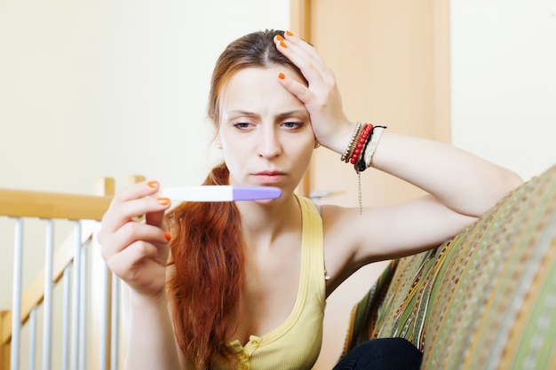 Serious girl with pregnancy test