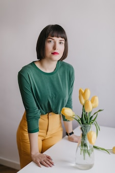 Serious girl with trendy makeup standing near table with flowers on it. interested white female model posing beside yellow tulips.
