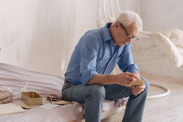 Serious gloomy aged man sitting in his bedroom and opening an old letter while turning over his mail