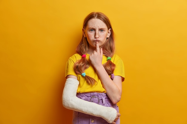 Serious gloomy girl keeps index finger under lower lip, has serious dissatisfied expression, freckled skin, dressed in summer outfit, thinks deeply about something, has broken arm after falling down