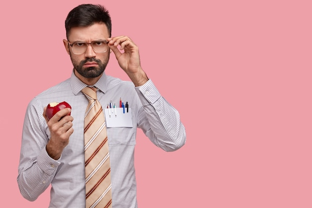 Serious gloomy male boss in formal clothes keeps hand on spectacles, bites delicious red apple