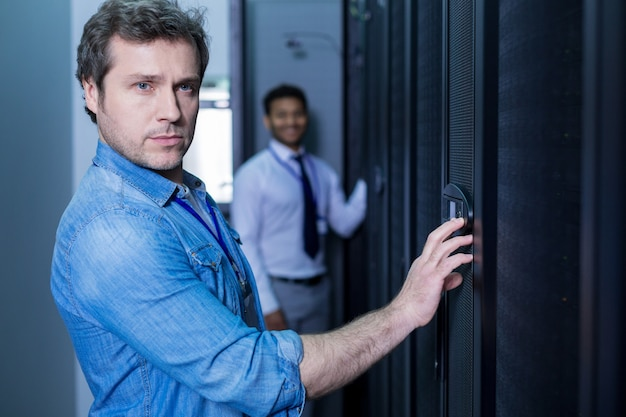 Serious good looking adult man entering the code and pressing the button on the control panel while opening the door of the network server