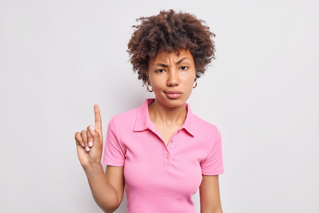 Serious good looking afro american woman with curly hair attracts your attention upwards points index finger above has displeased face expression wears casual pink t shirt isolated on white wall