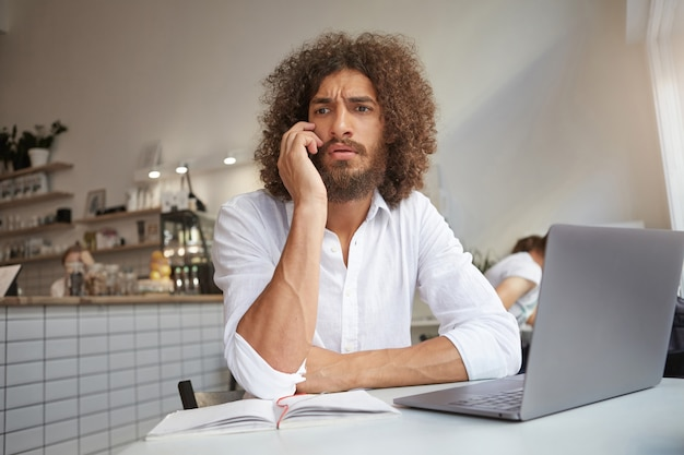 Serious good looking curly male with lush beard sitting at table in coffee room working out of office with modern laptop, frowning while serious phone conversation