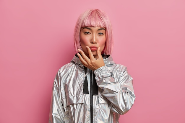 Serious good looking woman has eastern appearance, presses lips with hand, looks directly, dressed in stylish silver jacket, has trendy pink hairstyle, poses indoor. face expressions