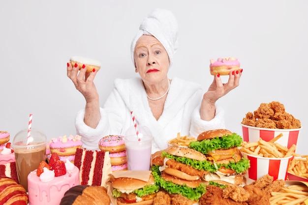 주름진 피부를 가진 진지한 할머니가 글레이즈드 도넛 두 개를 들고 있다