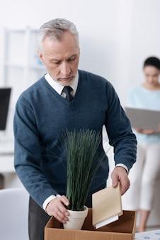 下向きに見ながら彼のノートと植物を箱のお辞儀の頭に入れている深刻な白髪の男