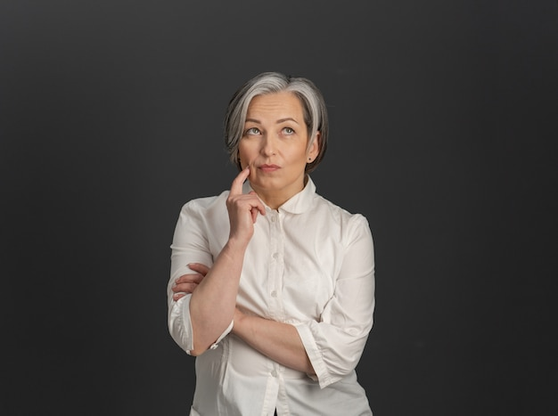 Serious gray-haired woman thinks looking up while touching her cheek with hand. thoughtful middle-aged woman in white shirt cut out on gray back. copy space on both sides