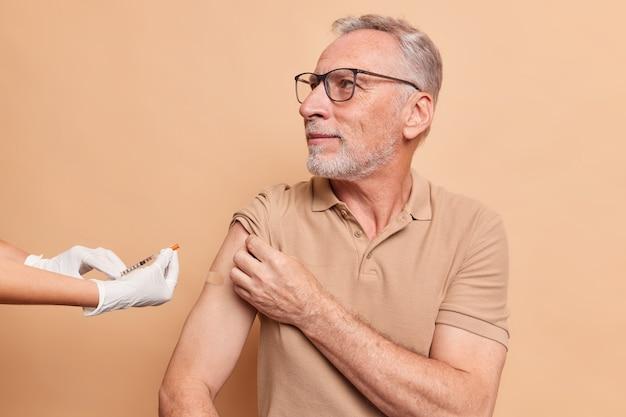 深刻な白髪の老人がコロナウイルスに対するワクチンを接種し、眼鏡をかけ、茶色の壁に隔離された看護師を注意深く見つめる
