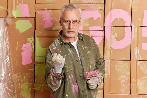 Serious grey haired handyman in glasses paints walls of room with brush busy with home renovation or apartment decoration clenches fist and looks direclty at camera wears clothes dirty with paint