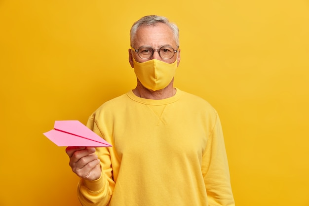 Serious grey haired man looks directly at front wears transparent glasses protective mask and holds paper airplane dressed in casual yellow jumper being infected with coronavirus