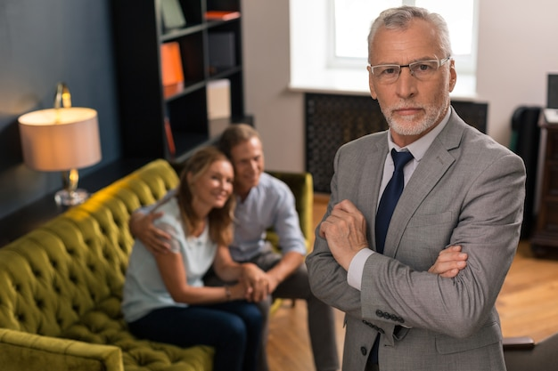 Serious grey-haired professional psychotherapist standing next to smiling patients in his office while looking at the camera