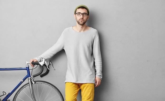 Ragazzo serio vestito con disinvoltura, vendendo biciclette moderne, tenendo le mani sul manubrio, dimostrando la sua buona qualità per i clienti. giovane sportrsman che va in un'altra città con la sua bici. concetto di equitazione