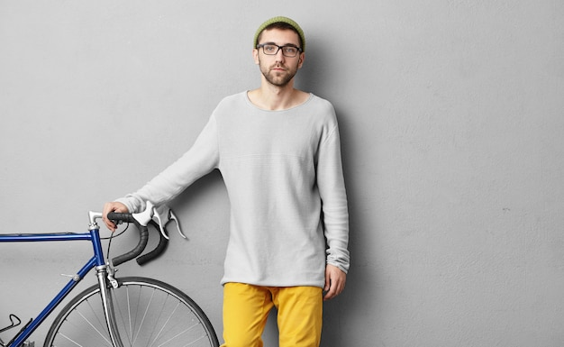 Серьезный парень одевается небрежно, продавая современный велосипед, держа руки на руле, демонстрируя его хорошее качество покупателям. молодой спортсмен собирается в другом городе на своем велосипеде. концепция верховой езды