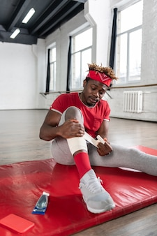 トレーニング中にトラウマを抱え、石膏で脚を覆っている深刻な男